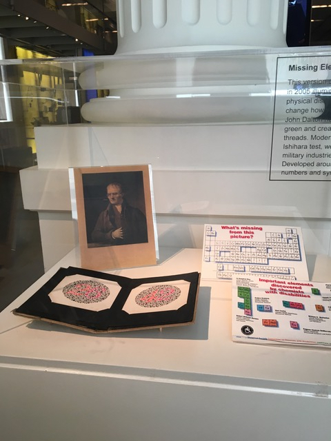 This is a color photograph of an exhibition vitrine with artifacts inside at the Science History Institute. In the top left corner is a portrait of chemist John Dalton. Below that are two plates containing the Ishihara color blindness test. These plates have a circular field in which dots of various sizes and hues are evenly distributed. To the right are periodic table charts showing which elements were discovered by disabled scientists.