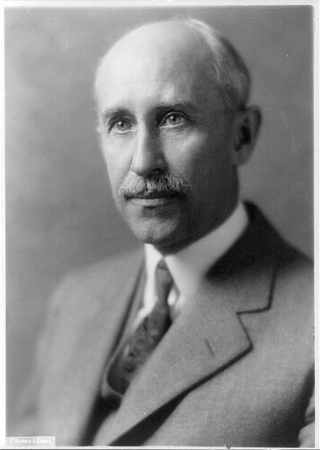 This is a black and white portrait of Orville Wright, a suit-wearing balding, mustached man with greying hair. He is facing partially left.