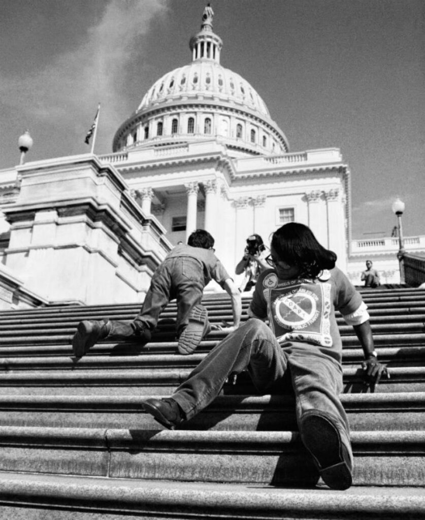 Black and white photo of two disabled people crawling p the capitol steps