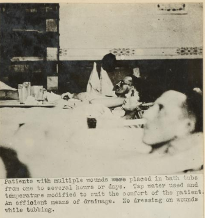 The black and white photograph shows three men lying in baths indoors.