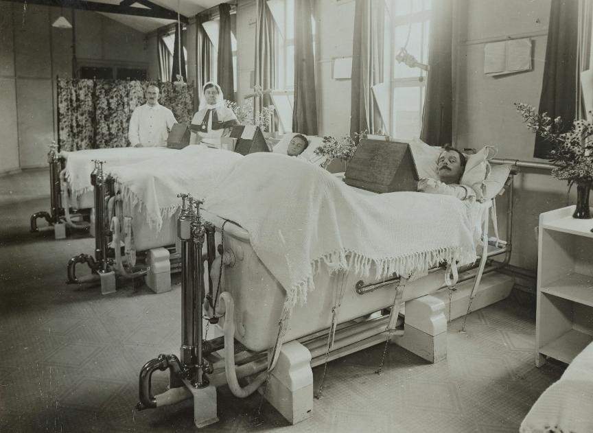 The black and white photograph shows an indoor scene in a hospital, with two men lying in baths and a nurse and a man in a white coat standing in the back of the frame.