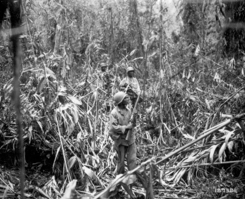 The black and white photo shows a densely forested jungle, and in the center of the photo are three African American soldiers carrying rifles and packs.