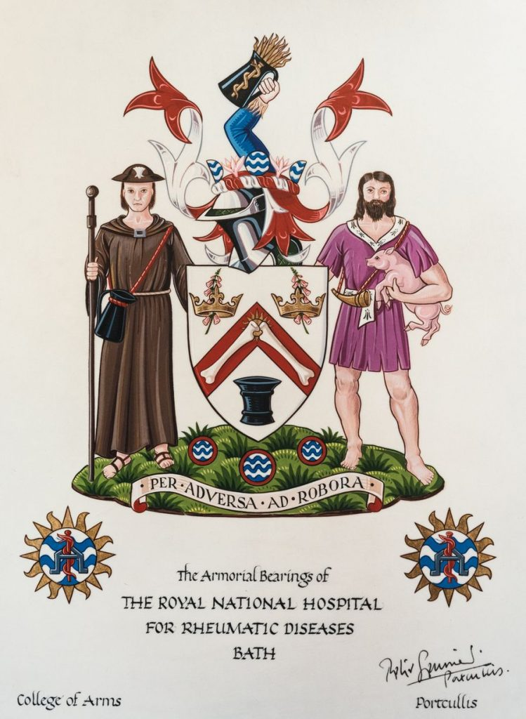 "A white shield with a red chevron featuring two bones on top. In the top corners are two crowns, in the lower point is a pipe. There are ribbons, armour and arms holding wheat protruding from the top of the shield and on either side are two men. The one on the left is wearing a brown floor length robe and hat, while carrying a long wooden stick and a small bag across his torso. The other man is bearded with long hair, wearing a much shorter purple robe and carrying a pig. They are all standing on a piece of grass, and a ribbon reads ""Per adversa ad robora""."