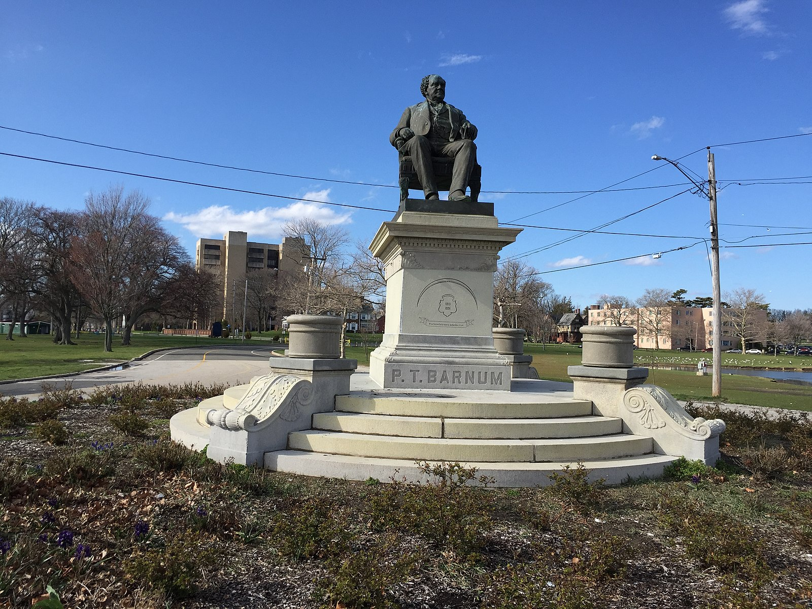 Statue of P.T. Barnum seating on a chair, placed on top of a column. There are stairs in front of the statue and grass around the area. In the background are some apartment buildings.