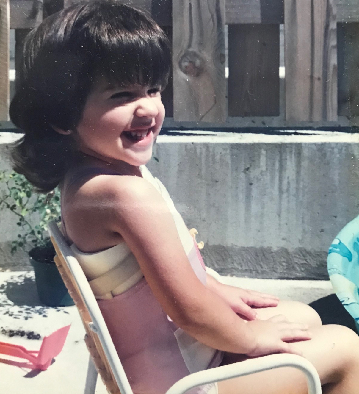 A young girl sits on a chair besides a pool. She has short dark hair and is wearing a chest brace. She is grinning.