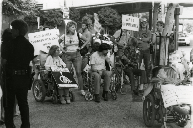 A group of disabled protestors, some in wheelchairs, standing in a street next to a freeway bridge. They are holding signs that says APTA Oppresses and Accessible Transportation Now!