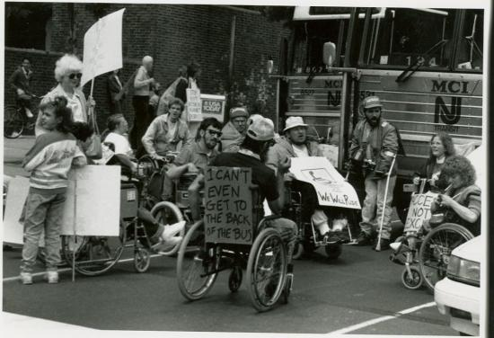 A group of disabled activists in wheelchairs or holding canes, standing in front of a bus labelled MCI NJ Transit. The activists are all holding protest signs. On the back of one man's wheelchair is a handwritten poster saying I can't even get to the back of the bus.