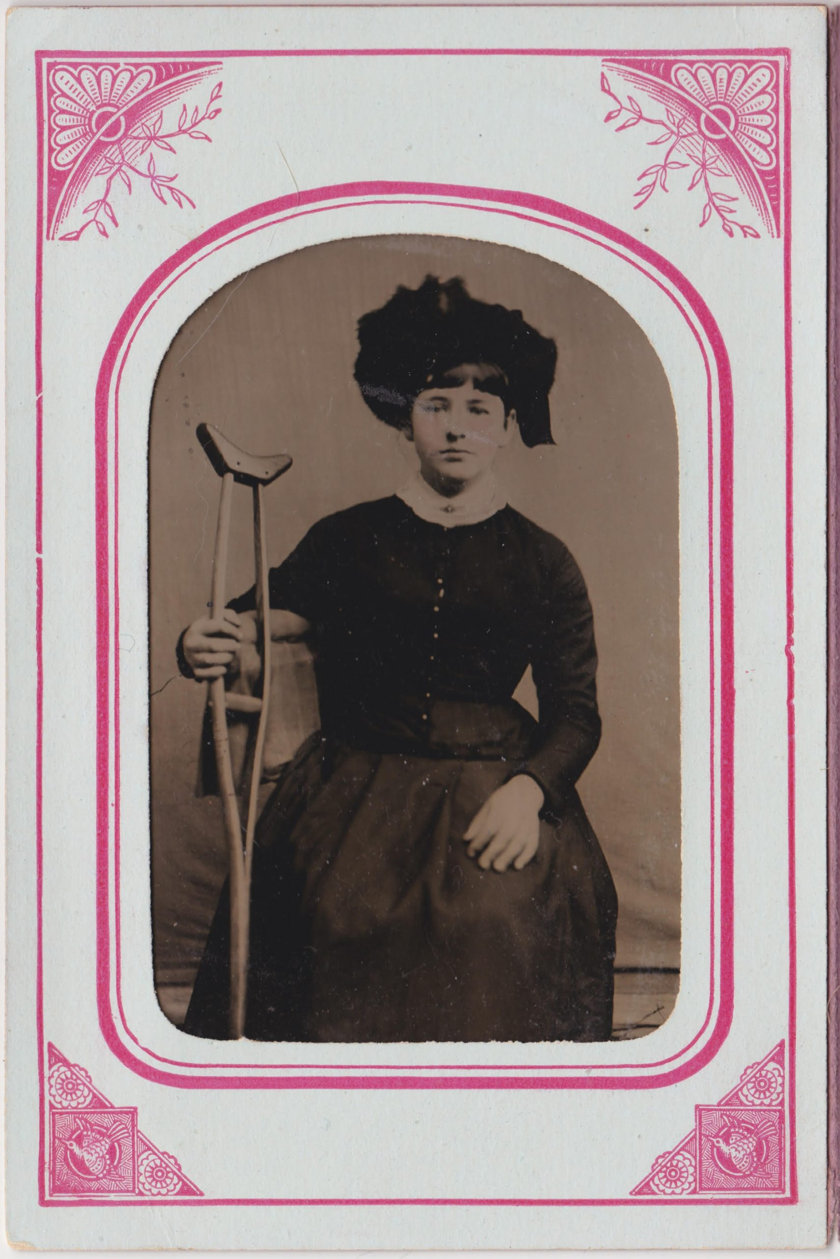 This is a black and white tintype of a woman sitting with a crutch in her right hand. Her left hand is resting on her knee. She is wearing a hat and gown with buttons (colored gold) down the bodice. The tintype is framed with white and red paper border. The border features stylized floral and bird designs in the corners.