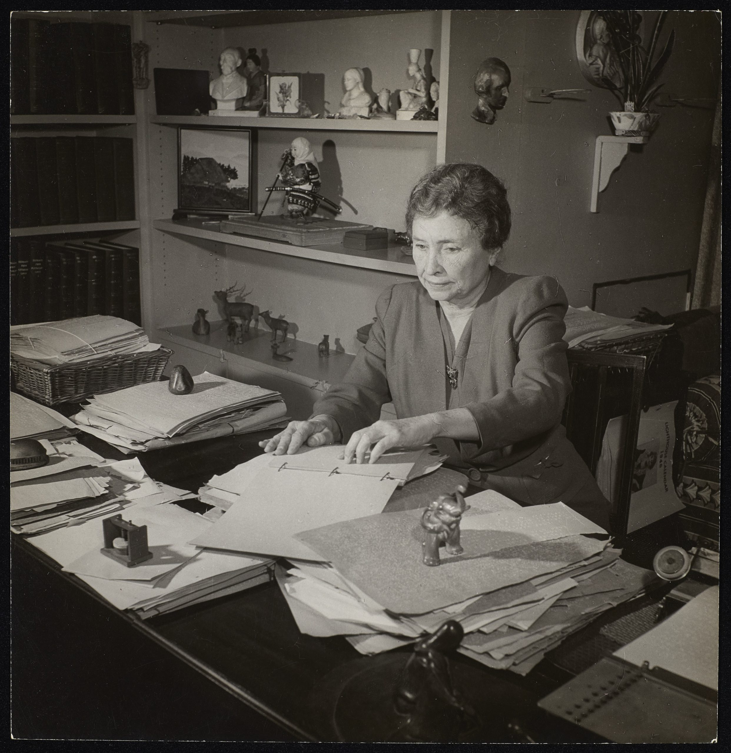 Helen Keller is reading text in braille. She is seated at her desk at her home.
