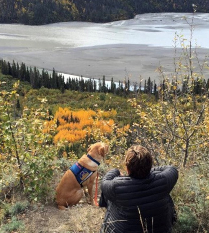 Judy Kesler with her service dog overlooking the Copper River in Wrangell-St. Elias National Park & Preserve in Alaska, National Park Service.