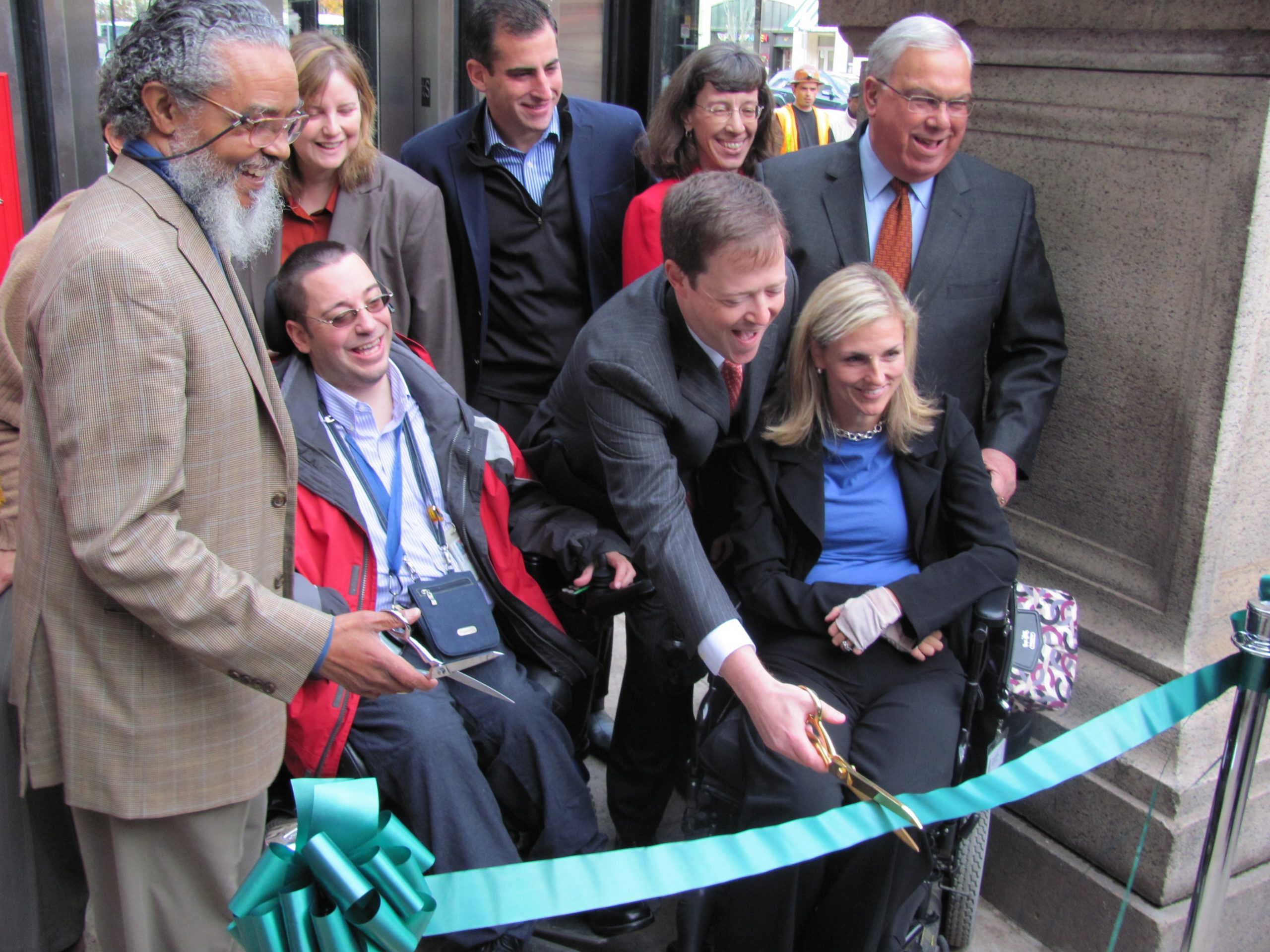 A group of predominantely white people at a ribbon cutting