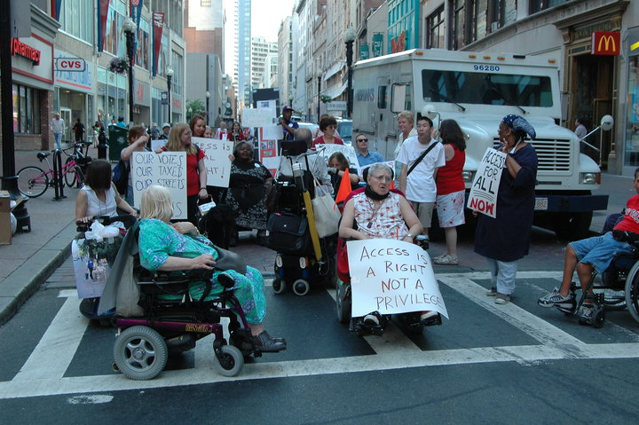 A group of people in wheelchairs and standing, holding signs, blocking a narrow street.
