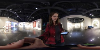 Woman with brown hair wearing a red and black paid shirt looking down at iPhone reaching out towards camera. Standing in an exhibit room with white walls and a dark ceiling.
