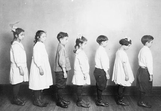 Group of children of varying height and genders standing against a wall, all are facing to the right direction and in poor posture position.