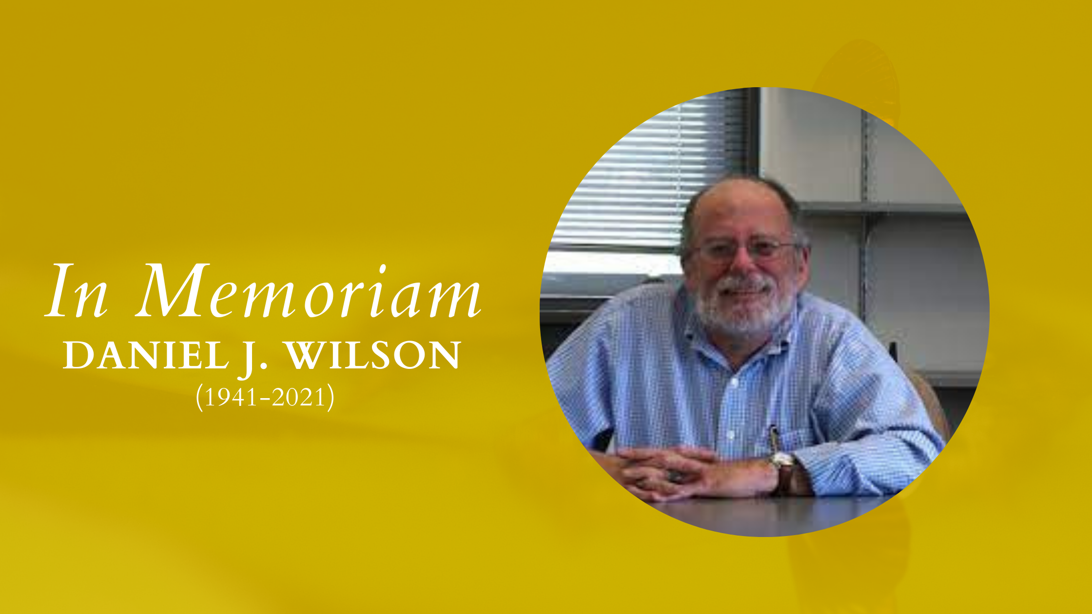 """A header banner with yellow graphic on the left, upon which white text is placed: """"In Memoriam Daniel J. Wilson (1941-2021)"""" On the right is a photograph of Dan, a bespectacled white man with white hair and beard. He is wearing a blue collared shirt, siting at a desk with his hands resting and interlocked, and smiling."""