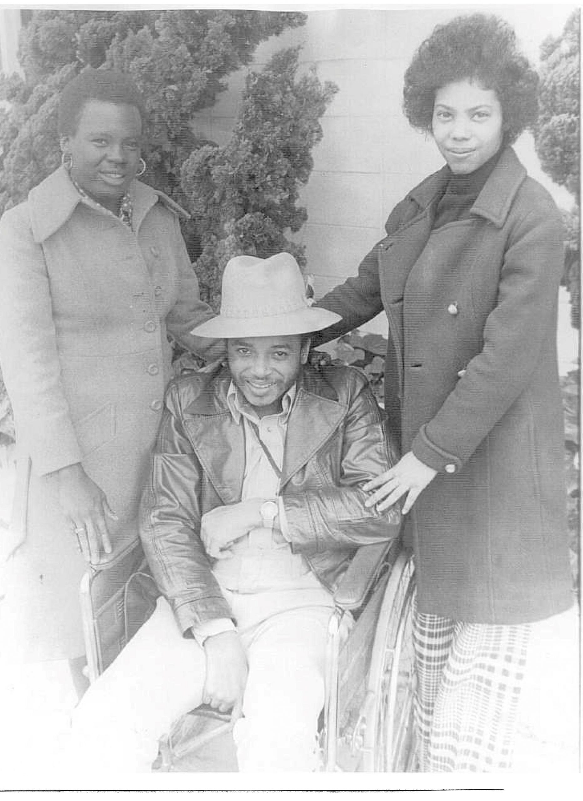 Two Black women, Barbara P. and Arlene C. standing on either side of Brad Lomax, a Black man who is seated in a wheelchair.
