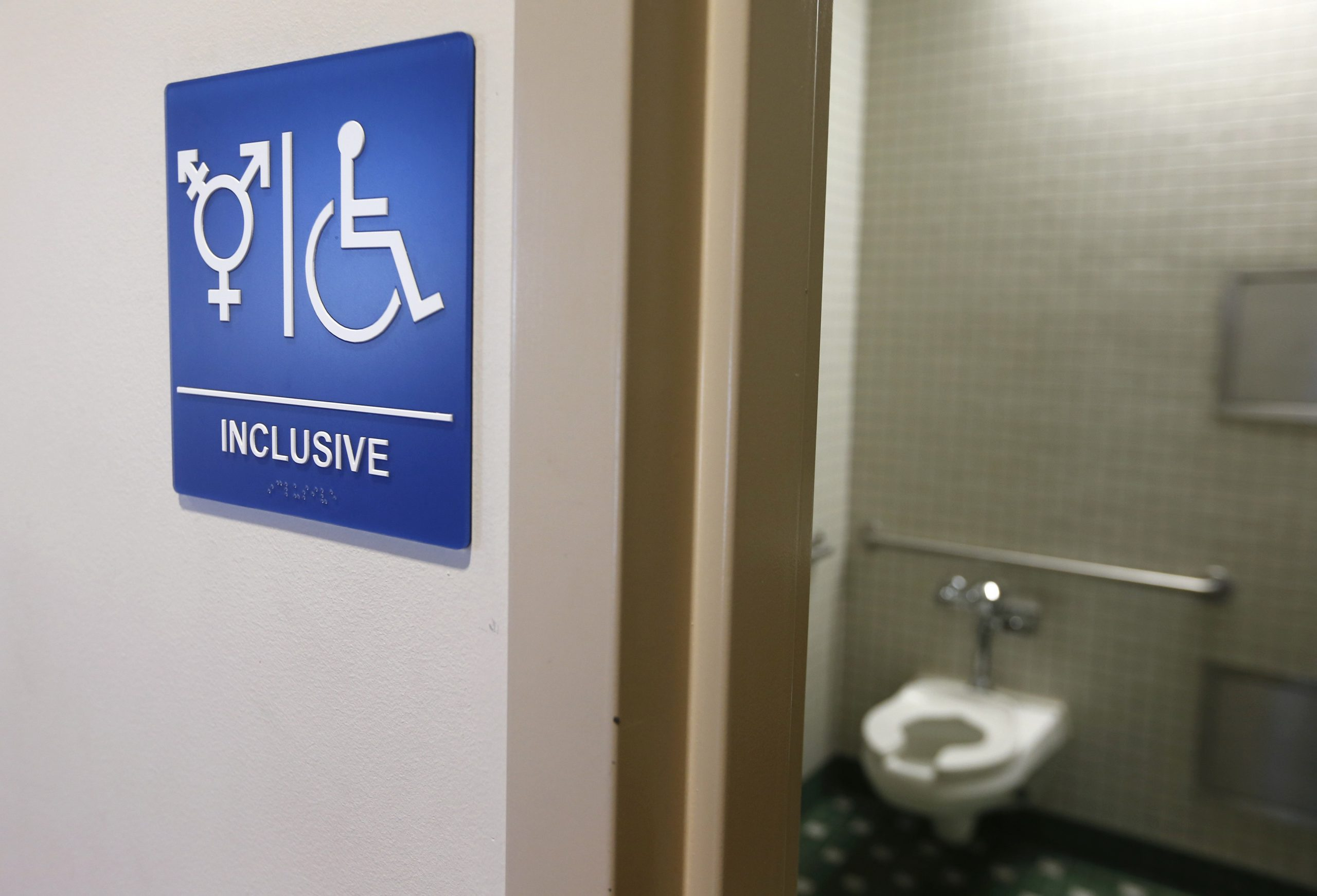 """Photo of bathroom with sign that says """"Inclusive"""" and has trans and disability icon"""