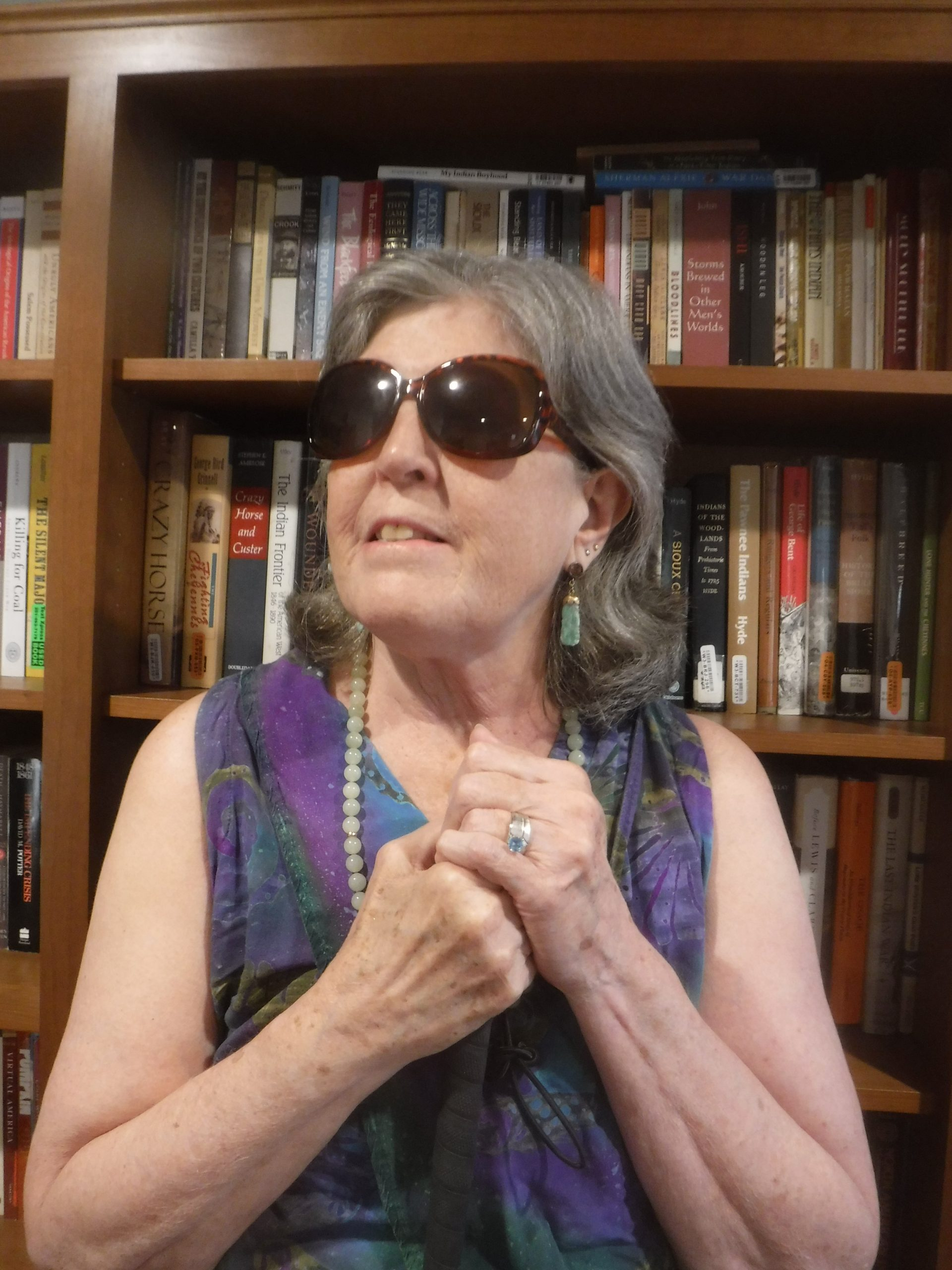The author, a white woman with short grey hair, stands in front of a bookshelf. She is wearing dark sunglasses and holding on to a cane.