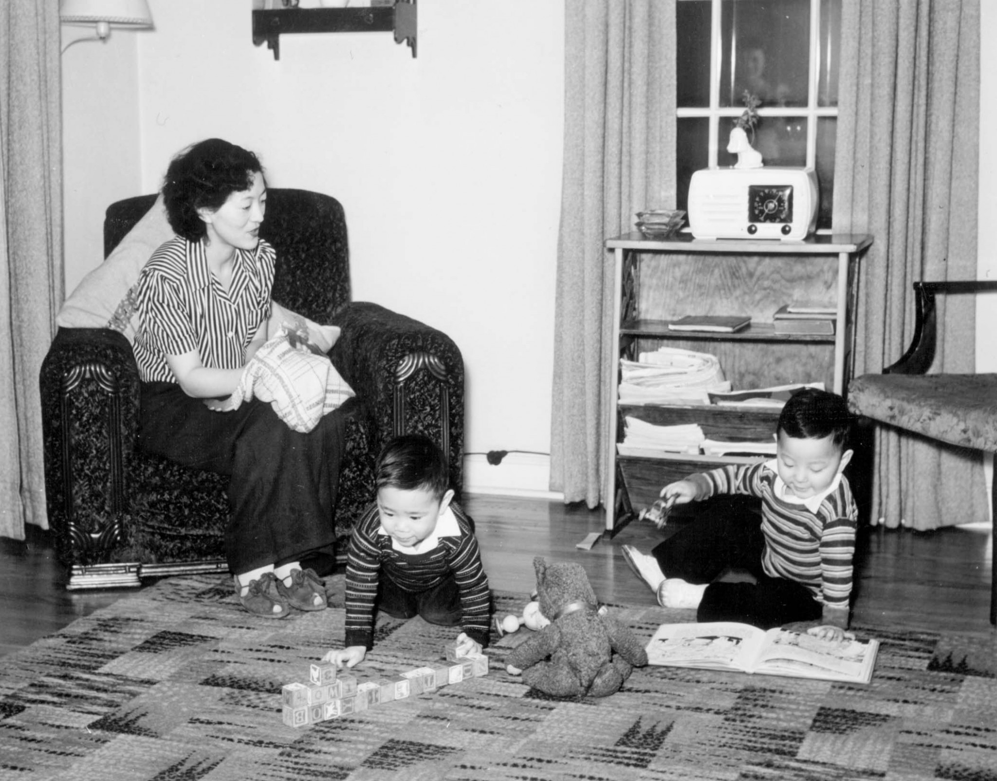 Photograph of a japanese american woman sitting on a sofa in the interior of her home, while two small boys are playing blocks and reading a book on the carpeted floor.
